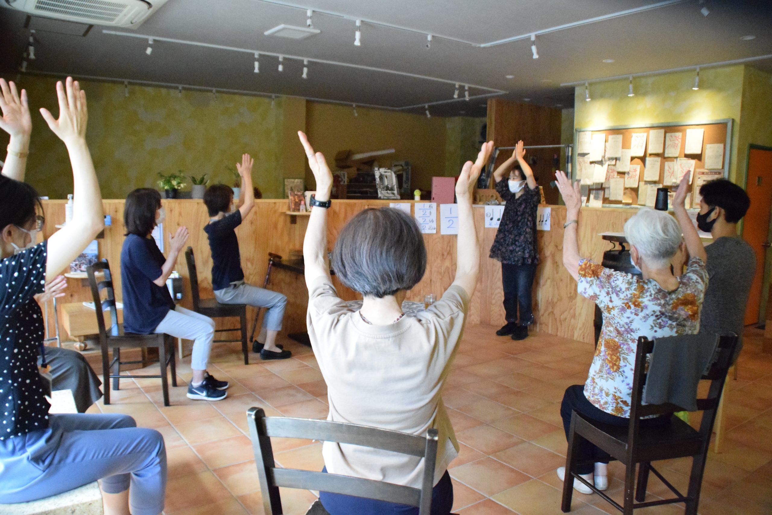 輪になって座る参加者。手を伸ばしている。